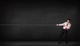 Веревочка бизнесмена вытягивая на серой предпосылке Стоковая Фотография