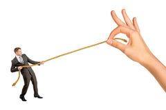 Веревочка бизнесмена вытягивая против большой руки женщины Стоковые Фотографии RF