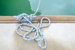 Веревочка зачаливания связанная вокруг стального анкера на шлюпке или корабле Стоковые Фото