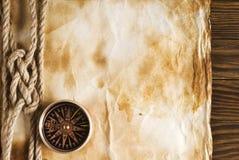Веревочка и компас на старой бумаге Стоковые Фото