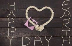 Веревочка и стикер в форме сердца влюбленности с текстом: Счастливая концепция дня земли Стоковое Фото
