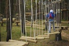 Веревочка мальчика взбираясь в лесе Стоковое Изображение