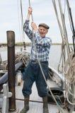 Веревочка пожилого рыболова вытягивая на палубе Стоковая Фотография
