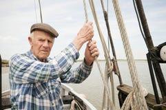 Веревочка пожилого рыболова вытягивая на палубе Стоковые Изображения RF