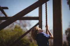 Веревочка решительно девушки взбираясь во время полосы препятствий Стоковые Фотографии RF