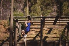 Веревочка решительно девушки взбираясь во время полосы препятствий Стоковое фото RF