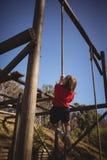Веревочка решительно девушки взбираясь во время препятствия courseDetermined веревочка девушки взбираясь во время препятствия co Стоковое Изображение RF