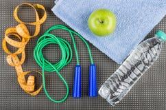 Веревочка скачки, лента измерений, зеленое яблоко на полотенце и воды Стоковая Фотография RF