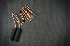 Веревочка скачки на черной циновке йоги Стоковая Фотография RF