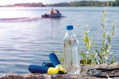 Веревочка скачки, стетоскоп и бутылка с водой на утесе с рекой Стоковая Фотография