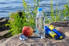 Веревочка скачки, яблоко, стетоскоп и бутылка с водой на утесе с Стоковые Изображения RF