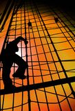 ВЕРЕВОЧКИ КОРАБЛЯ СИЛУЭТА ЧЕЛОВЕКА МАТРОСА ВЗБИРАЯСЬ ПРОТИВ НЕБА ЗАХОДА СОЛНЦА ЗОЛОТА Стоковое фото RF