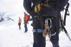 Веревочки рюкзака и безопасности в горах Snowy с 2 друзьями ах Стоковое Изображение