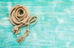 Веревочки связанные с узлами на предпосылке бирюзы Стоковая Фотография