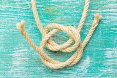 Веревочки связанные с узлами на предпосылке бирюзы Стоковая Фотография RF