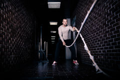 Веревочки фитнеса сражая на тренировке фитнеса разминки спортзала сделанной красивым хорошим смотря человеком Веревочки Crossfit  Стоковое Фото