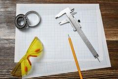 Верньерный масштаб, карандаш, желтые защитные стекла и 2 подшипника лежа на чертежной бумаге на деревянной предпосылке Стоковое Фото