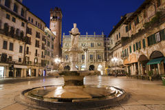 Верона - фонтан на аркаде Erbe в сумраке и Porta Leona и Palazzo Maffe Стоковые Фотографии RF