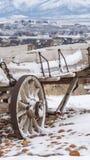 Вертикальная старая деревянная фура с цепями и ржавыми колесами запыленными со снегом в зиме стоковые фотографии rf