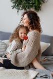 Вертикальная съемка ласковой молодой матери и ее daugher обнимают один другого и срочная влюбленность, сидит на удобной кровати стоковые фотографии rf