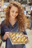 Вертикальная съемка приятной смотря довольной женщины держит коробку с очень вкусными конфетами шоколада, выбирает десерт для тог стоковая фотография