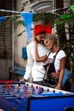 Вертикальная съемка приятной смотря смешанной гонки женской и ее одина другого объятия парня, стоит близко футбольная игра таблиц стоковые фотографии rf