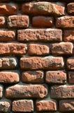 Вертикальная текстура стены нескольких строк очень старой кирпичной кладки сделанной красного кирпича Разрушенная и поврежденная  Стоковое фото RF