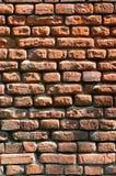Вертикальная текстура стены нескольких строк очень старой кирпичной кладки сделанной красного кирпича Разрушенная и поврежденная  Стоковые Изображения RF