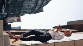 Вертикальное видео Портрет снаружи привлекательной уверенно бизнес-леди стоящего используя связь smartphone онлайн видеоматериал