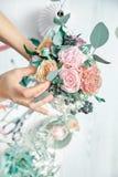 Вертикальное изображение женского флориста на работе Аранжировать различные цветки в букете r Учитель floristry в мастерских клас стоковая фотография rf
