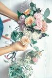 Вертикальное изображение женского флориста на работе Аранжировать различные цветки в букете r Учитель floristry в мастерских клас стоковая фотография