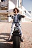 Вертикальное изображение счастливой курчавой девушки сидя на современном мотоцилк Стоковое фото RF