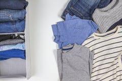 Вертикальное хранение одежды, tidying вверх, концепция комнаты очищая Стог сложенных одежд в корзине с unholded кучей стоковое фото