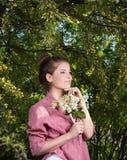 Вертикальный портрет молодой женщины с ветвью ubder цветений сирени дерево Стоковые Фото