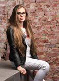 Вертикальный портрет стильной молодой женщины Белые джинсы и черная кожаная куртка Стоковые Изображения RF