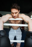 Вертикальное изображение утомленного боксера ослабляя в боксерском ринге Стоковые Изображения