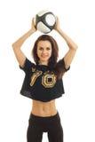Вертикальный портрет молодой жизнерадостной девушки с футбольным мячом в руках усмехаясь на камере Стоковое Изображение RF