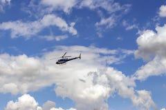 Вертолет летает против предпосылки белых облаков в голубом небе Стоковая Фотография