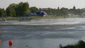 Вертолет спасения пожарной команды носит воду в танке сток-видео