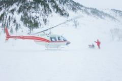 Вертолет приземлился люди в горах в зиме, поднимая Стоковое Изображение RF