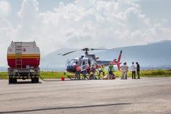 Вертолет людей дозаправляя Стоковые Фото