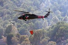 Вертолет Firefighting летает над, который сгорели землей Стоковое Изображение RF