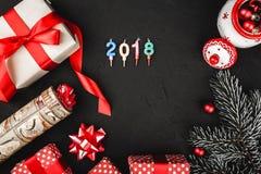 Верхнее взгляд сверху красной ленты, настоящий момент, handmade игрушка Санты и вечнозелёное растение разветвляют на каменной чер Стоковые Фото