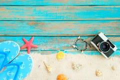 Верхнее viwe песка пляжа при тапочка, морские звёзды, раковины, коралл, ретро camara и браслет сделанные seashells на голубом дер Стоковые Фото
