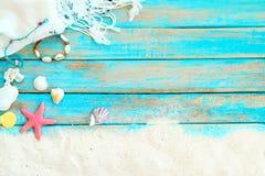 Верхнее viwe песка пляжа с белой шалью, браслетом сделанным seashells, морскими звёздами, раковинами и кораллом на голубой деревя Стоковое Фото