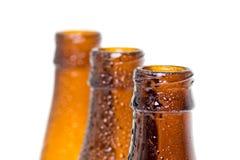 3 верхней части пивных бутылок с падениями 2 воды Стоковая Фотография
