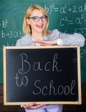 Верхние пути приветствовать студентов назад к школе Надпись классн классного владением женщины учителя назад к школе Школьное вре стоковая фотография