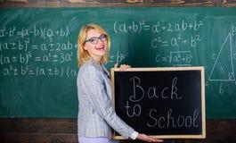 Верхние пути приветствовать студентов назад к школе Надпись классн классного владением женщины учителя назад к школе Школьное вре стоковое изображение