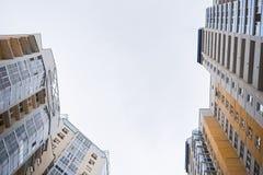 Верхние части взгляда низкого угла фасадов ярких современных сер-желтых жилых домов Стоковые Фото