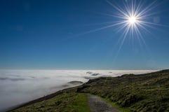Верхние части холма над облаками стоковые фото